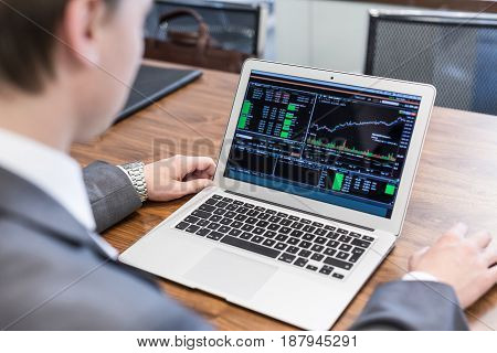 Corporate businessman analyzing economic data on laptop computer. Man's hands on notebook computer, business person at workplace.