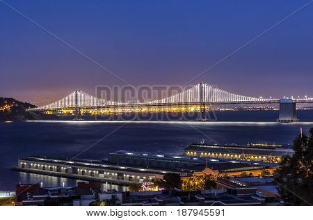 The bridge is glowing in the early night over the bay.