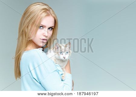 girl or pretty woman with long blond hair hairstyle holding cute cat or kitten pet fluffy domestic animal in arms on grey background. Friendship and care. Veterinarian copy space