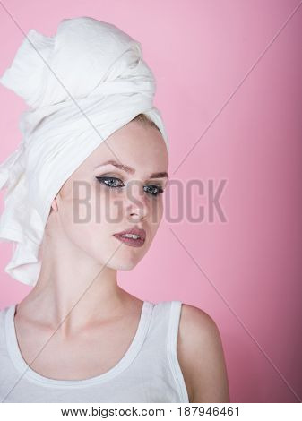 girl or pretty woman with stylish makeup and white bath towel on head posing on pink background. Haircare spa beauty hygiene