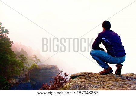 Hiker In Squatting Position On A Rocky Peak And Enjoy The Misty  Scenery