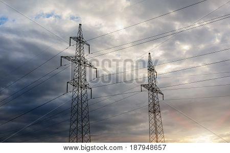 a high voltage power pylons against blue sky and sun rays