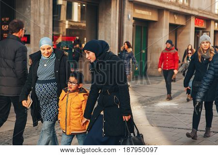 Munich, Germany, December 29, 2016: A friendly family of migrants walks down the street in Munich. Tolerance, friendliness