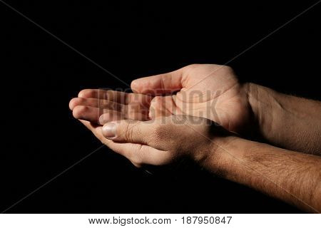 Male hands on a black background, close up