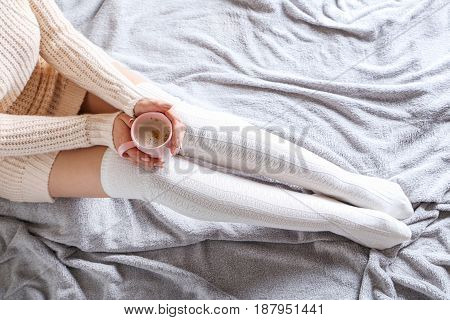 Woman with cup of coffee sitting on the bed