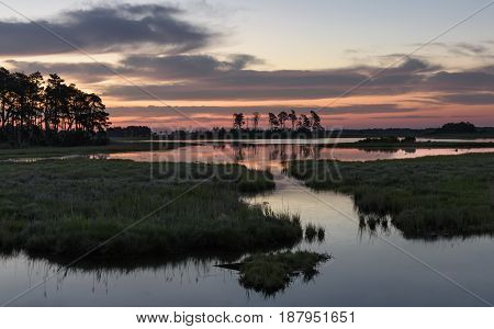 Dramatic Sunrise with Clouds Reflecting in Water of Salt Marsh