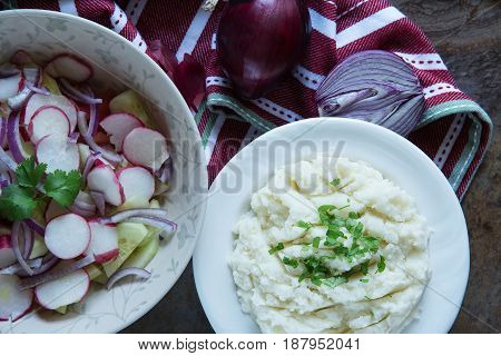 healthy salad with fresh ripe summer vegetables tomato cucumber radishes spices and mashed potatoes on black stone slate background