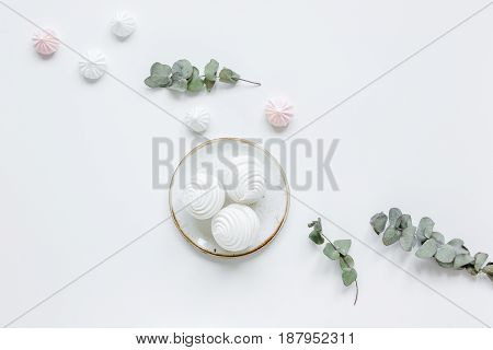 woman lunch with marsh-mallow in plate and flowers trendy design in soft light on white table background flat lay