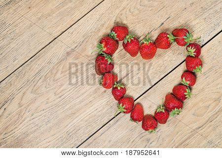 Ripe strawberries laid out on an old wooden table in the shape of a heart