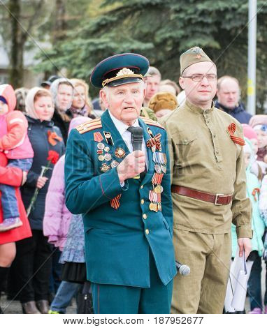 Kirishi, Russia - 9 May, ,A war veteran with a microphone, 9 May, 2017. Holding a festive rally dedicated to the Victory Day.