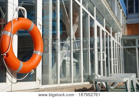 Orange lifebuoy on a wall of a protection of the swimming pool