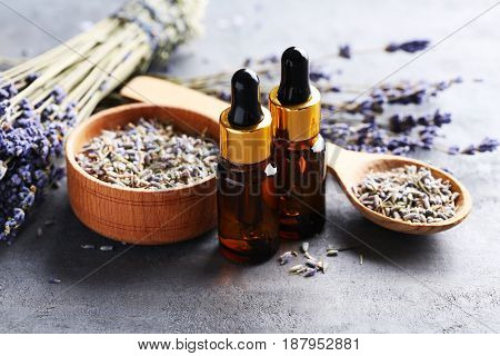 Lavender Oil And Flowers On Grey Table