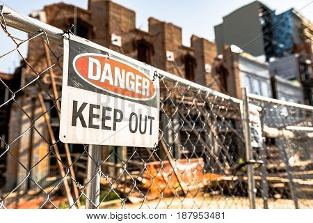 Danger Keep Out sign on a chain link fence in front of a dilapidated run-down building with supports to keep it from falling down.