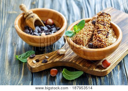 Cereal Bars And Chocolate Drops In A Wooden Bowls.