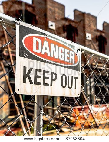 Danger Keep Out sign on a chain link fence in front of a dilapidated run-down building.