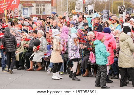Kirishi, Russia - 9 May, Teens carry flowers to veterans, 9 May, 2017. Holding a festive rally dedicated to the Victory Day.