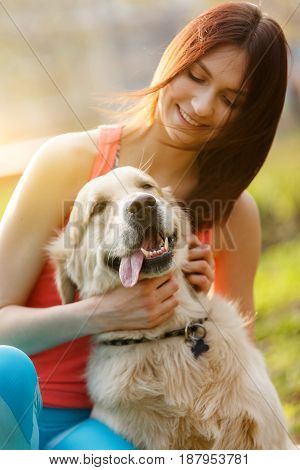 Portrait of brunette with dog in park