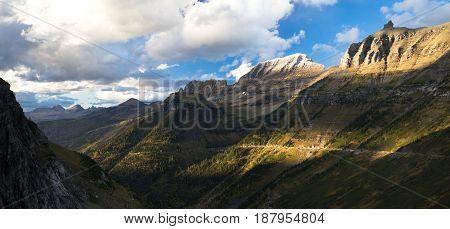 High peaks of the rocky mountains loom over the highway in Glacier National Park