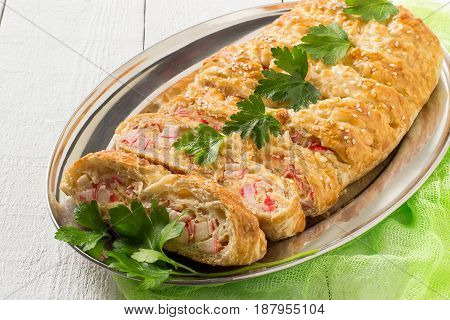 Delicious homemade pie made of puff pastry with cheese and surimi on metal tray. White wooden background green gauze napkin