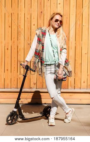 Blonde in checkered scarf with scooter against wooden fence