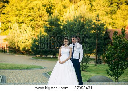 Young couple, bride and groom walking and enjoying their wedding day. Sunshine. Summer.