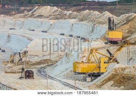 Mining excavators in the chalky quarry. Heavy chalk mining industry.