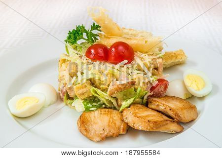 A Tasty Salad Of Vegetables, Herbs And Cheese, With Boiled Eggs And Pieces Of Fried Meat, On A White