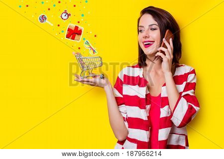 Young Woman With Shopping Cart And Mobile Phone