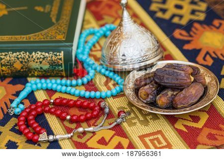 Red and turquoise rosaries dates and qur'an on carpet