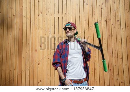 Man looks sideways with scooter on shoulder, standing at wooden fence in spring
