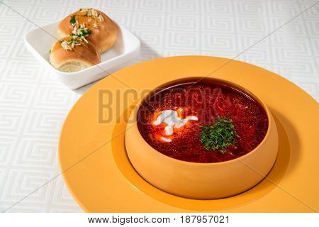 A Delicious Red Soup With Sour Cream And Herbs, In A Dark Yellow Plate, And Bread Rolls, On A White