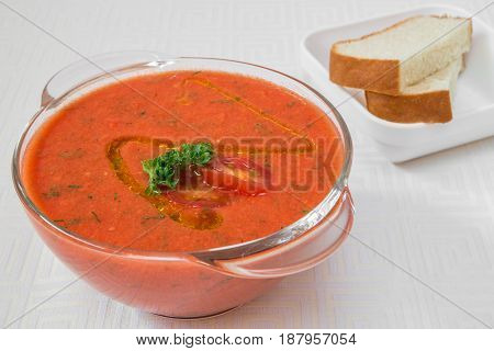 Delicious Red Soup With Herbs In A Transparent Plate, And Bread On A White Tablecloth. Horizontal Fr