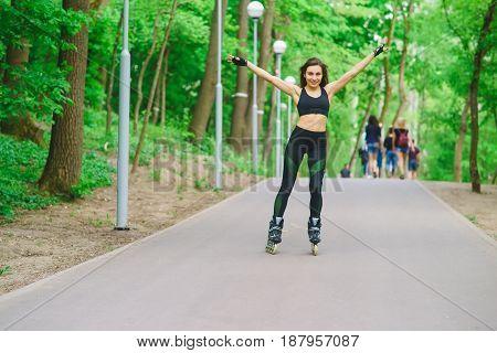 Sportive brunette girl in full-length rollerblading park posing