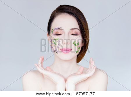 portrait of beautiful young woman with flowers on her face on the wonderful grey studio background