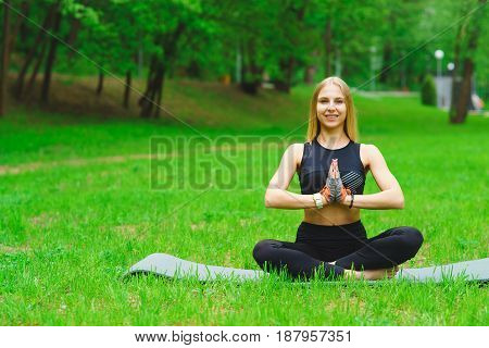 The brunette girl is engaged in yoga in the park in the fresh air and sits in a lotus pose