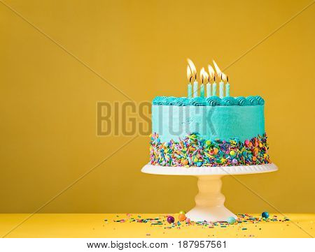Blue buttercream birthday cake with sprinkles over yellow background.