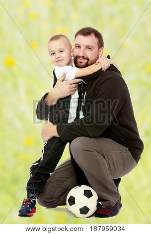 little boy who loves to play football embraces his beloved father.