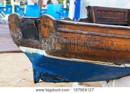 Old rotten wooden boat on the sand close-up.
