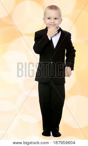 Beautiful little blond boy in a fashionable black suit with a tie.Boy what a thought.Brown festive, Christmas background with white snowflakes, circles.