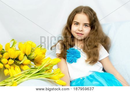 A beautiful little girl with long blond, flowing hair sits on the couch next to a large bouquet of yellow flowers, tulips.
