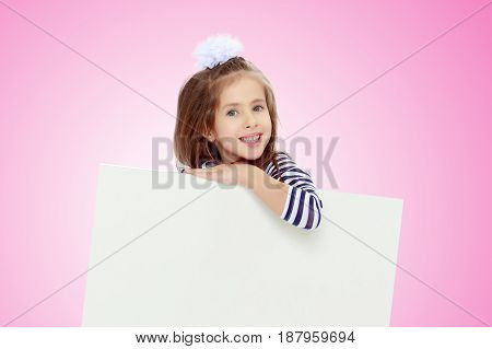 The little blonde girl with long hair and with a white bow on her head , in a blue striped summer dress.She peeks out from behind white banner.Pale pink gradient background.
