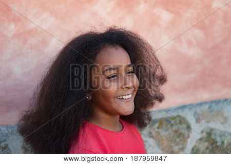 Pretty girl with long afro hair in the garden laughing