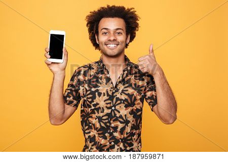 Portrait of a cheerful young afro american man showing blank screen mobile phone and giving thumbs up isolated over yellow background