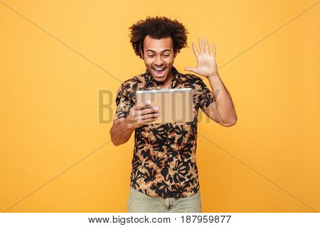 Portrait of an excited african man having video call through pc tablet and waving hand isolated over yellow background