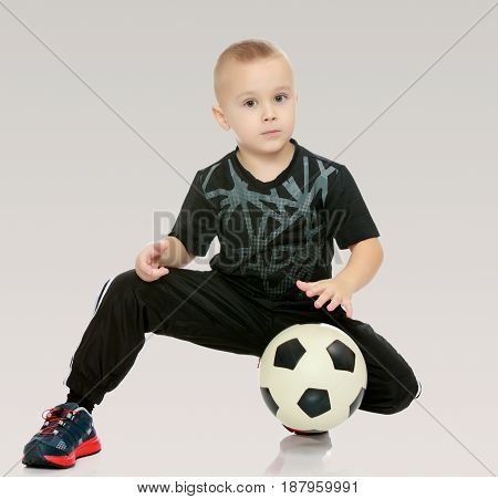 Cute little boy with the ball.The boy squats and holds the ball with his hands.On a gray background.