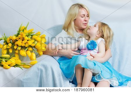Mother and daughter in identical blue dresses hugging sitting on the sofa.Next to them lies a large bouquet of yellow tulips.