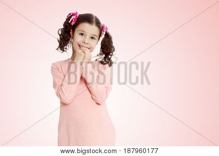 Beautiful little girl with long curly tails on the head, in which braided red ribbons . In long pink dress. The girl shyly holding hands near the face. Close-up.Pale pink gradient background.