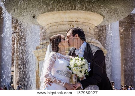 Bride and groom under the fountain at St. Peter's Square Rome Italy - May 2 2017
