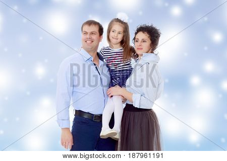 Happy young family, mom dad and little daughter.Parents keep the girl in her arms , and she hugs their neck.Blue Christmas festive background with white snowflakes.