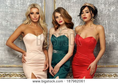 Three gorgeous stunning girls in mermaid evening dresses standing and posing in luxury interior. Brunette, blonde and red hair young elegant woman.
